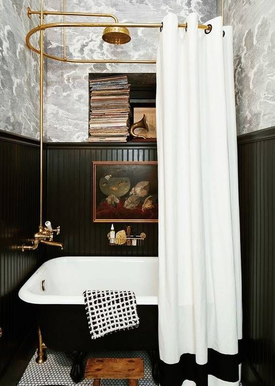 a small and chic bathroom with grey wallpaper, black planks, a niche for storage, a small black tub and a curtain
