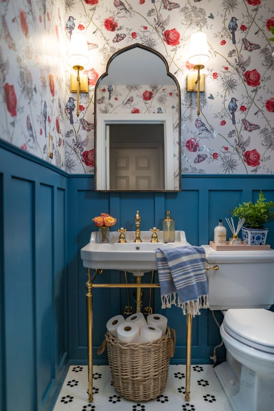a small and colorful powder room with floral wallpaper, blue panels, a console sink, white appliances, a catchy mirror and a basket with toilet paper