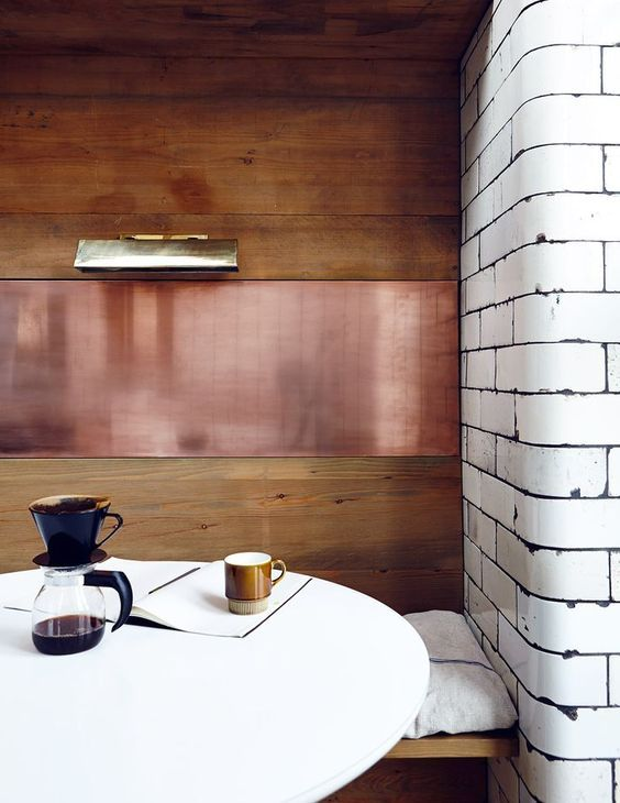 a small and cozy dining nook with a stained wood and copper wall, a round table and a built-in bench is a very cool solution