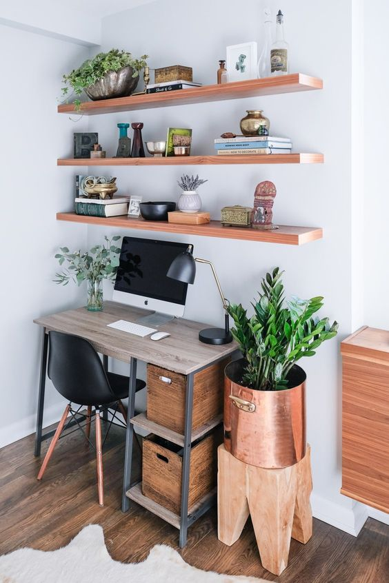 a small and cozy home office nook with open shelves, with an industrial desk, a black chair, a stool with a copper planter and lots of plants