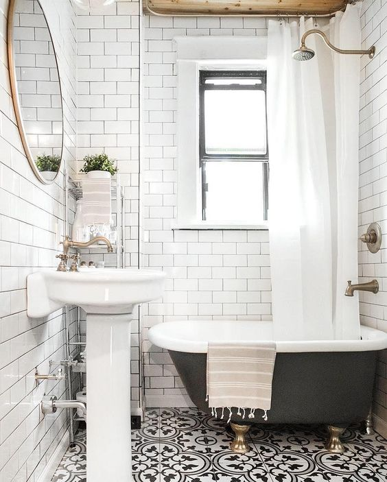 a small and cute bathroom with black and white tiles, white subway ones, a black clawfoot tub, a pedestal sink, a round mirror and a storage cart