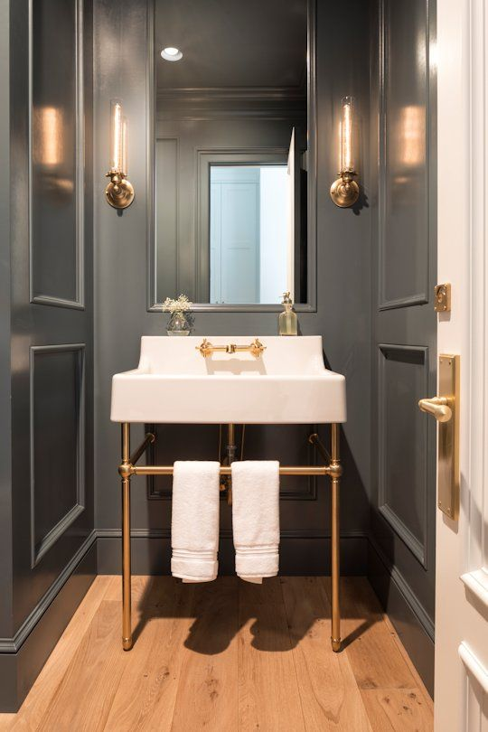 a small and elegant powder room with grey paneling, a console sink, chic sconces, white towels and touches of gold and brass