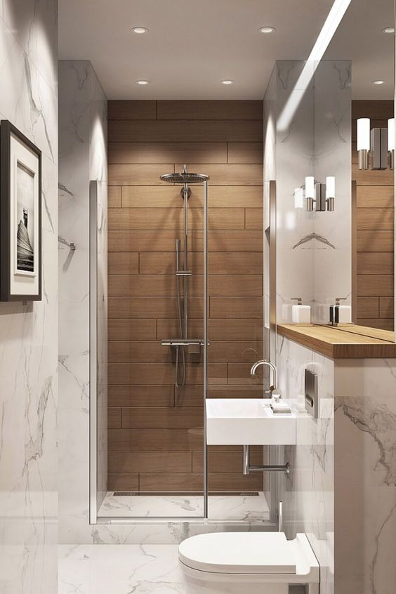 a small and refined bathroom clad with white stone tiles and with a wood tile accent in the shower, with white appliances and neutral fixtures