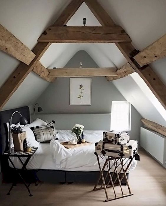 a small attic Scandi bedroom with wooden beams, a dark bed with neutral bedding, a folding nightstan and vintage suitcases for decor
