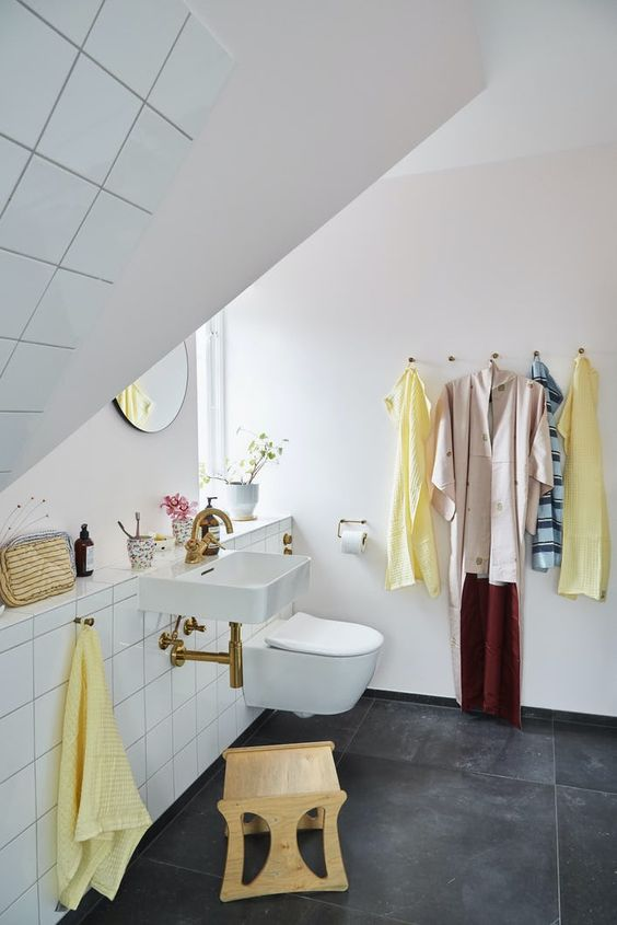 a small attic bathroom with black large scale tiles and white square ones, a floating sink, a round mirror and a plywood stool is cool
