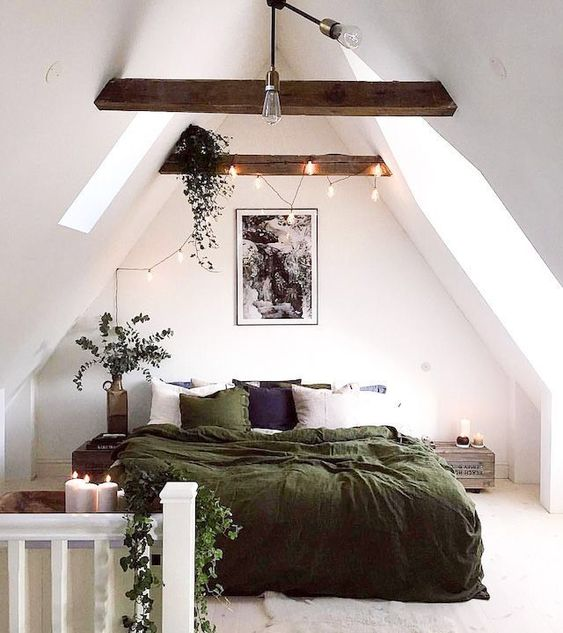 a small attic bedroom with dark-stained beams and lights on them, a bed with green bedding, reclaimed wood nightstands and potted plants
