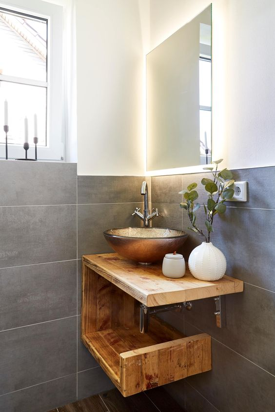 a small bathroom clad with concrete tiles, with wooden floors, a wooden vanity with a catchy and shiny vessel sink and a lit up mirror