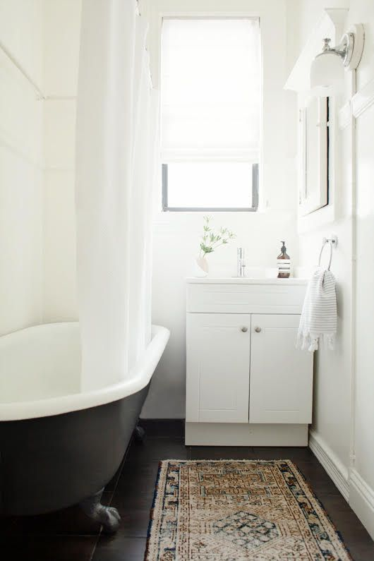 a small boho bathroom with white walls and a dakr-stained floor, a black clawfoot tub, a white vanity and neutral textiles is a chic idea