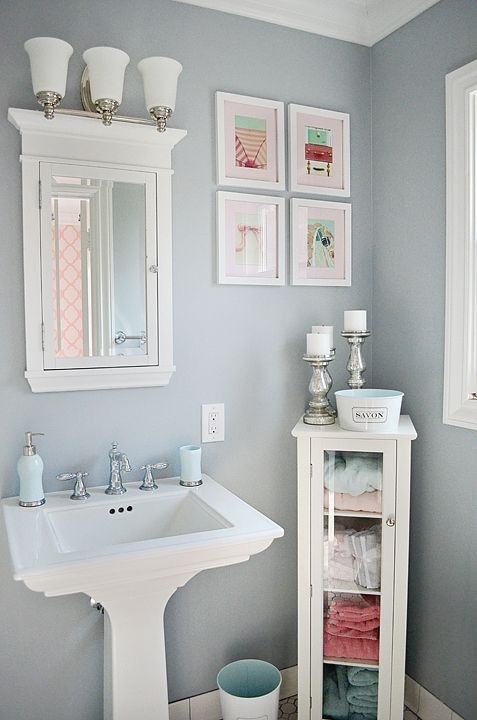 a small grey powder room with a pedestal sink, a small storage unit, a bright gallery wall and a small mirror cabinet plus a sconce