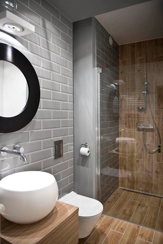 a small modern bathroom clad with grey and wood look tiles, a small shower space, a bowl sink, a round mirror and white appliances