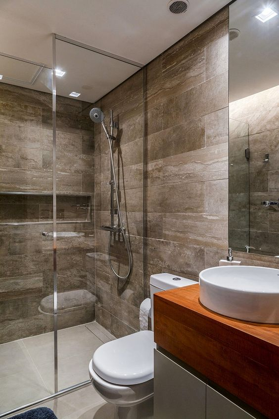 a small modern bathroom clad with wood look tiles, with concrete tiles on the floor, a white and stained vanity and white appliances