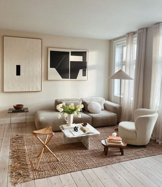 a small modern living room with a grey low sofa, a creamy chair, a stone coffee table, a leather stool and a bold gallery wall