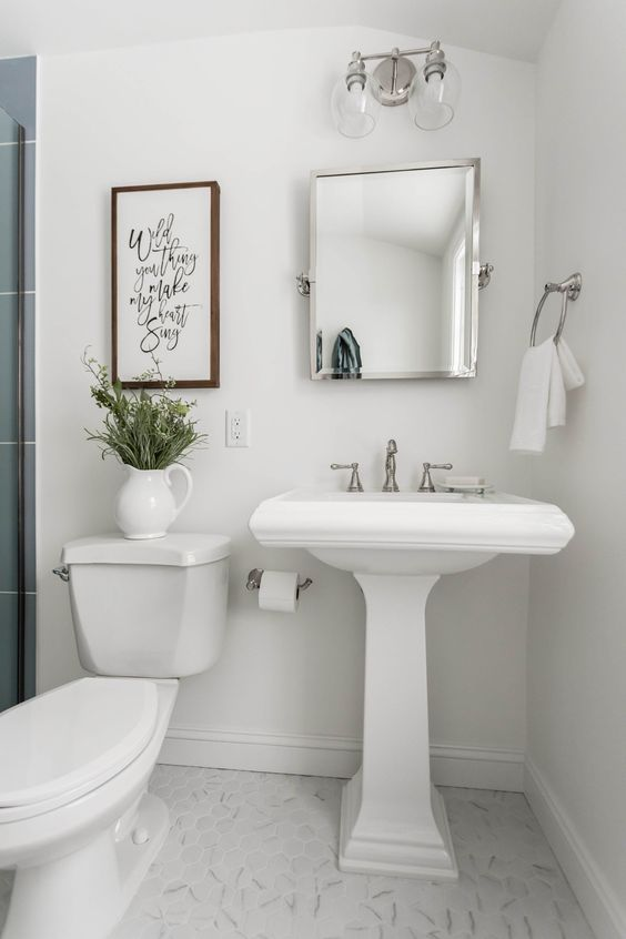 a small neutral bathroom with a pedestal sink, a mirror cabinet, a sconce, greenery, a sign and a shower space with blue tiles