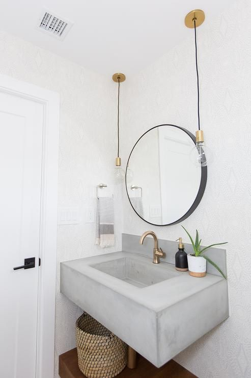 a small powder room with a concrete sink and vanity in one, a round mirror, pendant bulbs, a basket and brass and gold fixtures