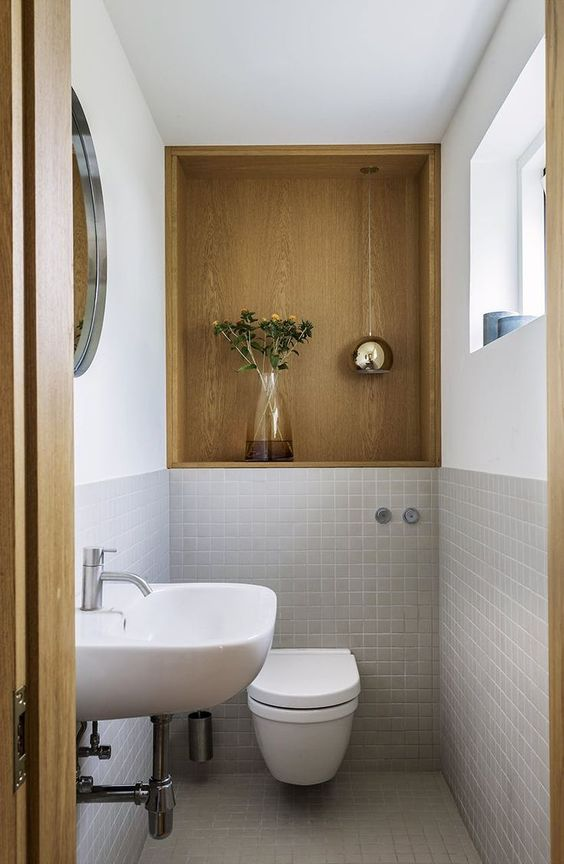 a small powder room with a plywood niche, grey tiles, white appliances including a white floating sink and a round mirror