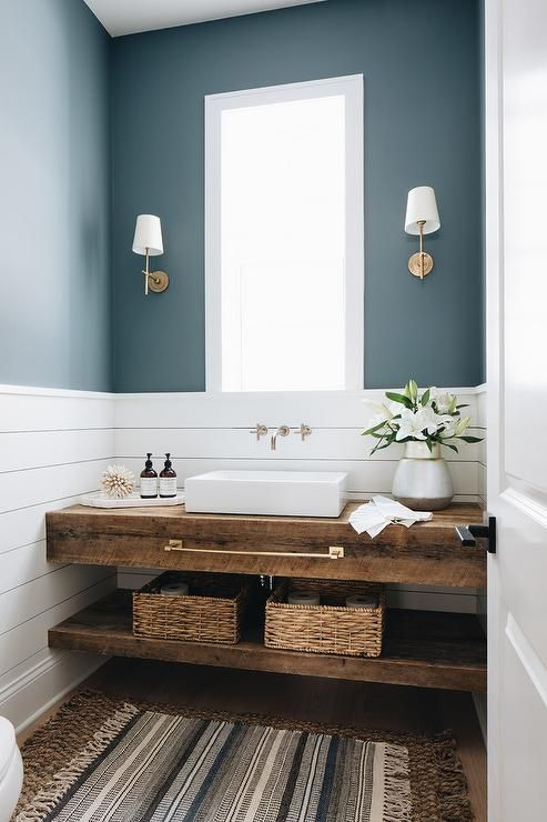 a small powder room with blue and white planked walls, a reclaimed wooden vanity, a square vessel sink and sconces is chic