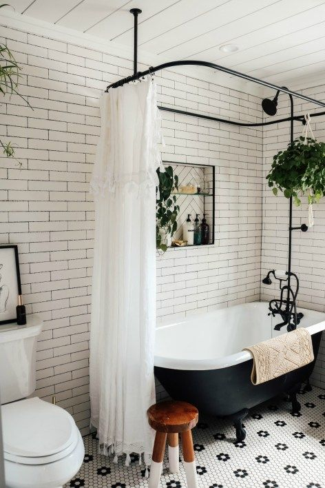 a small retro bathroom clad with white subway and penny tiles, a vintage black tub, black fixtures and potted plants is cool