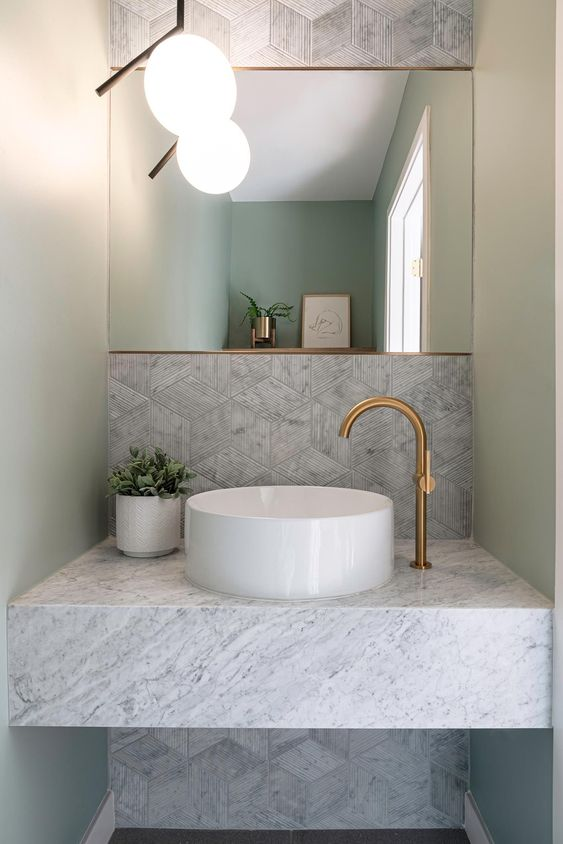 a sophisticated bathroom with grey geo tiles, a marble slab vanity with a round vessel sink and a cool mirror