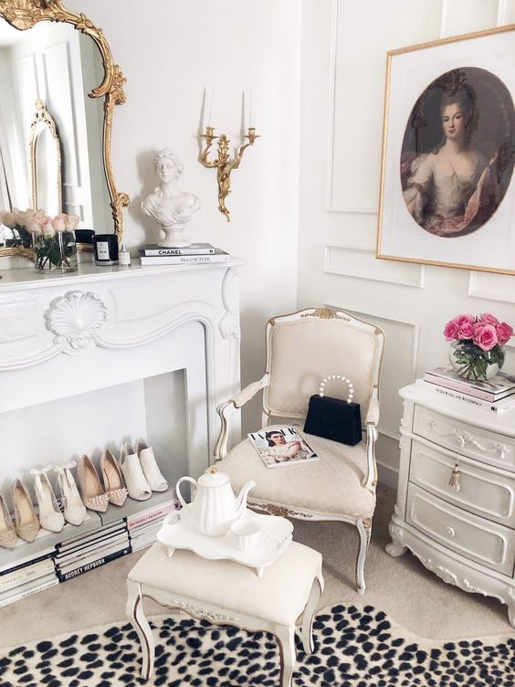 a sophisticated closet space with paneled walls, a chic dresser, neutral refined furniture, a vintage fireplace used for displaying shoes on magazines