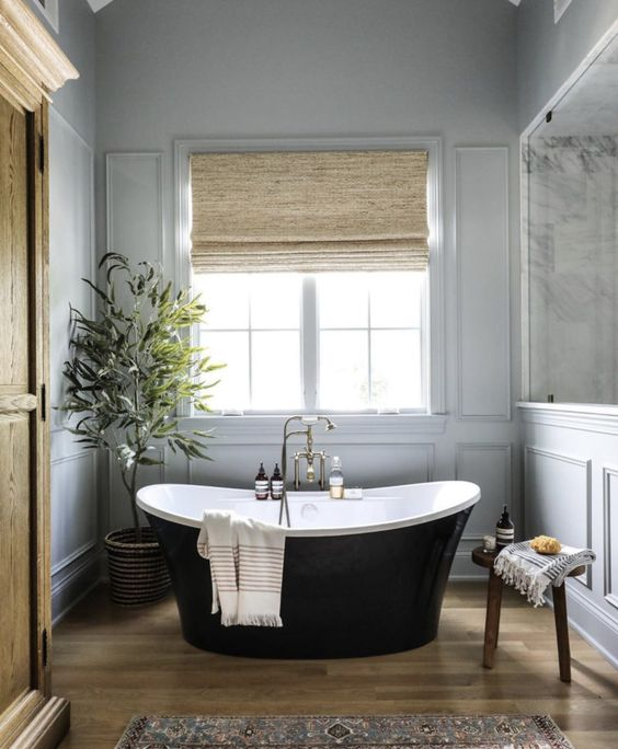 a sophisticated neutral bathroom with grey panels on the walls, a sleek black tub, shades, a printed rug and alight-stained wardrobe