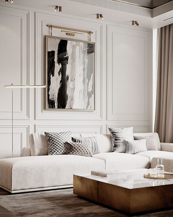 a sophisticated neutral living room with paneled walls, a creamy sectional, a low coffee table and a bold statement artwork is wow