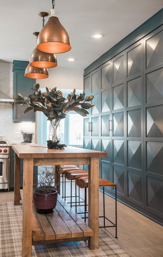 a stained and rough wood kitchen island, leather stools, copper pendant lamps for a cozy and rustic feel