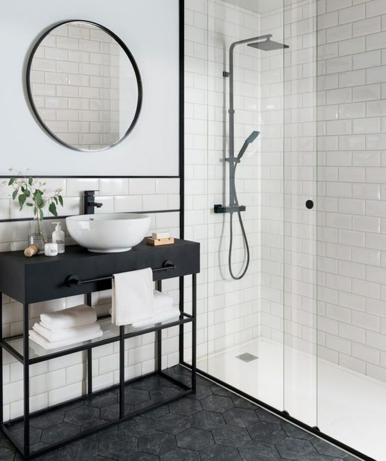 a stylish bathroom clad with subway and hex tiles, a console sink, a round mirror, black fixtures looks laconic and chic