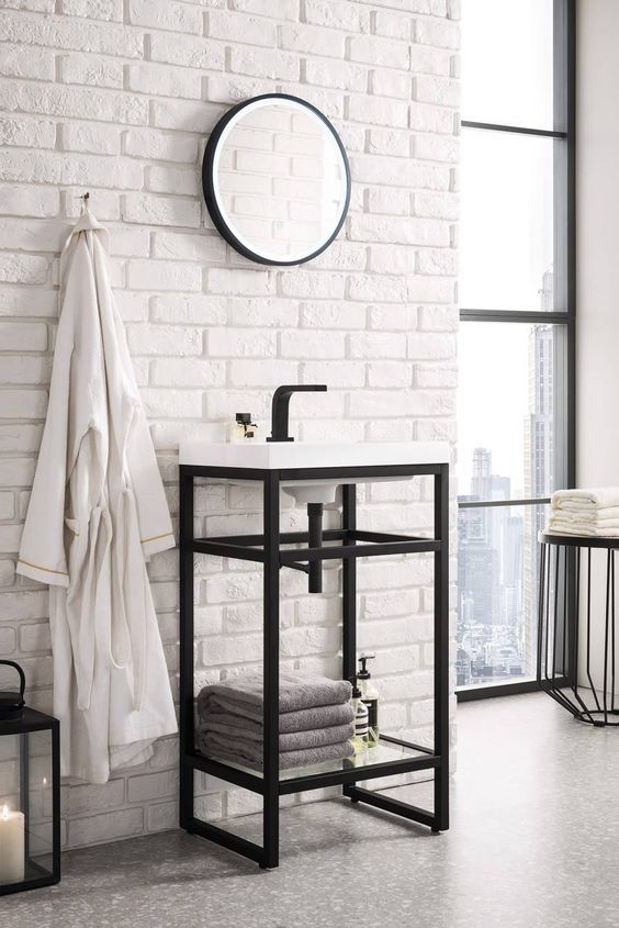 a stylish bathroom with faux white brick, a console sink, a round mirror in a frame, a black lantern and neutral textiles