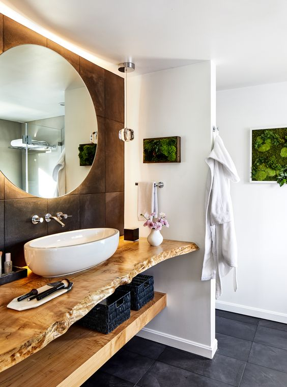 a stylish bathroom with natural touches - vertical planters and a living edge open vanity, an oval vessel sink and a round lit up mirror