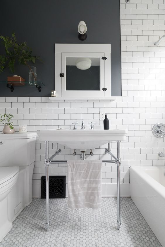 a stylish black and white bathroom clad with penny and subway tiles, with black walls, white appliannces and a console sink