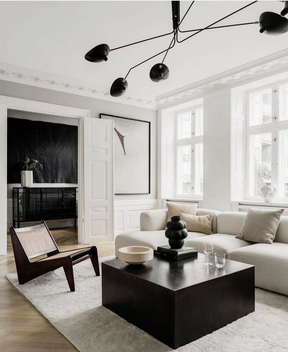 a stylish black and white living room with paneling, a white low sofa, a black slab table and a chic chair plus a statement chandelier