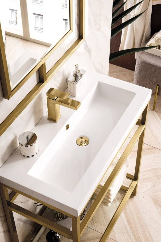 a stylish console sink with a console made of brushed brass and a white sink, a brushed brass faucet and a matching mirror for ultimate elegance