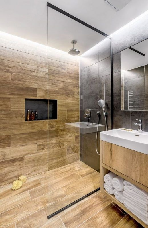 a stylish contemporary bathroom clad with black stone and wood look tiles, a niche, a light stained vanity and white appliances