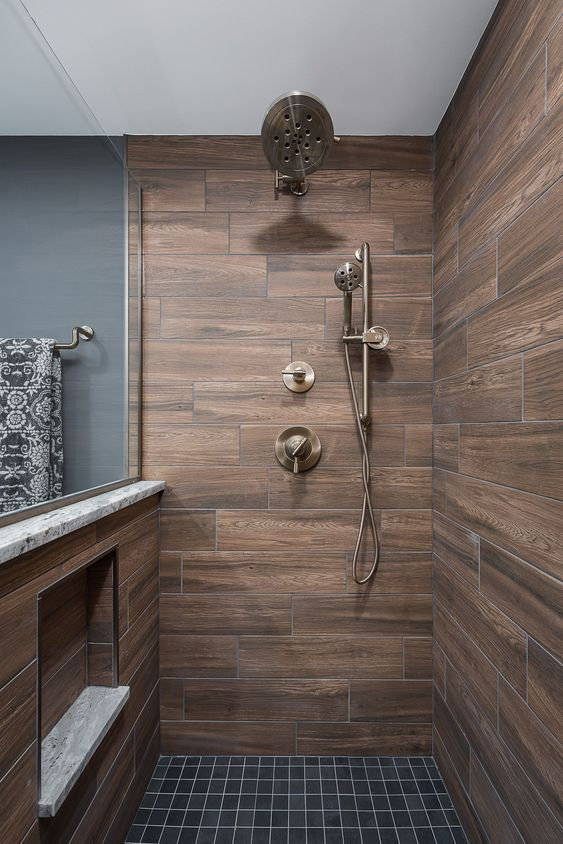 a stylish contemporary bathroom clad with wood look tiles and graphite grey ones, brass fixtures is a cool and bold idea with chic