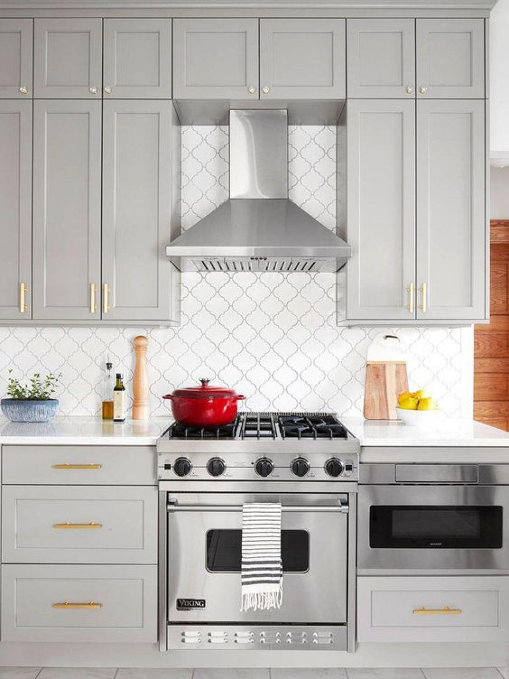 a stylish contemporary kitchen done in dove grey, with shaker cabients, gold handles, a white arabesque tile backsplash and black grout