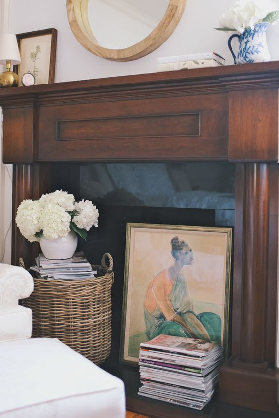 a stylish fireplace with a dark stained mantel, a stack of magazines, an artwork and a basket with books and blooms