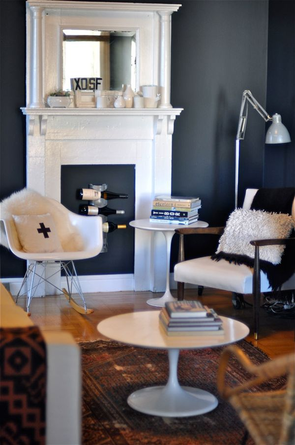 a stylish living room with grey walls, a faux fireplace that features a wine bottle rack, creative furniture and a bold printed rug