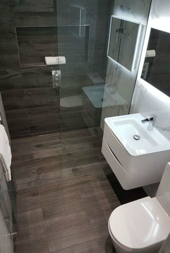 a stylish modern bathroom clad with marble and wood look tiles looks refined, with a lit up mirror, white appliances and a niche for storage