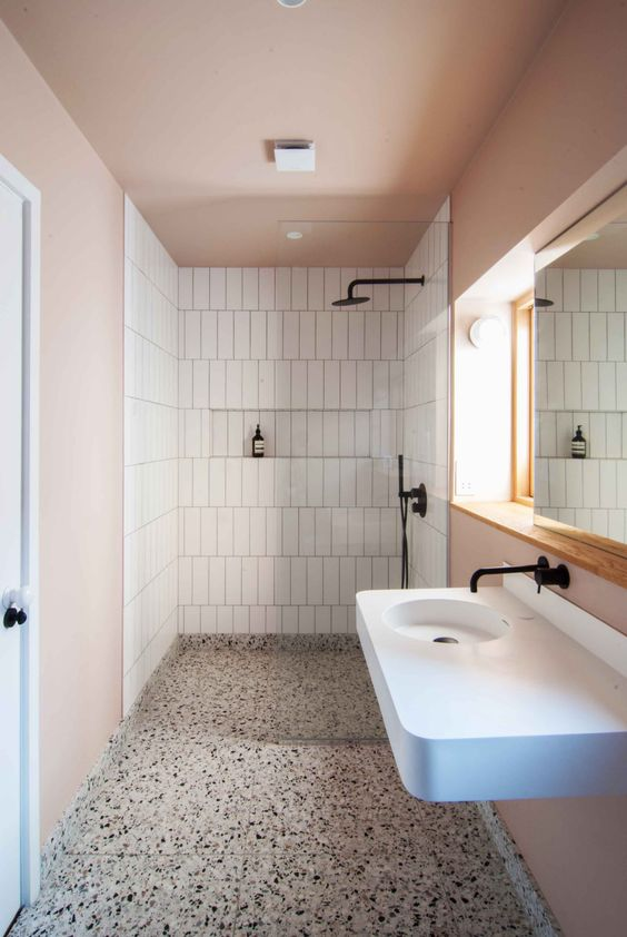 a stylish modern bathroom with pink walls and a ceiling, white skinny tiles, a terrazzo floor and a floating white sink with a vanity space and black fixtures