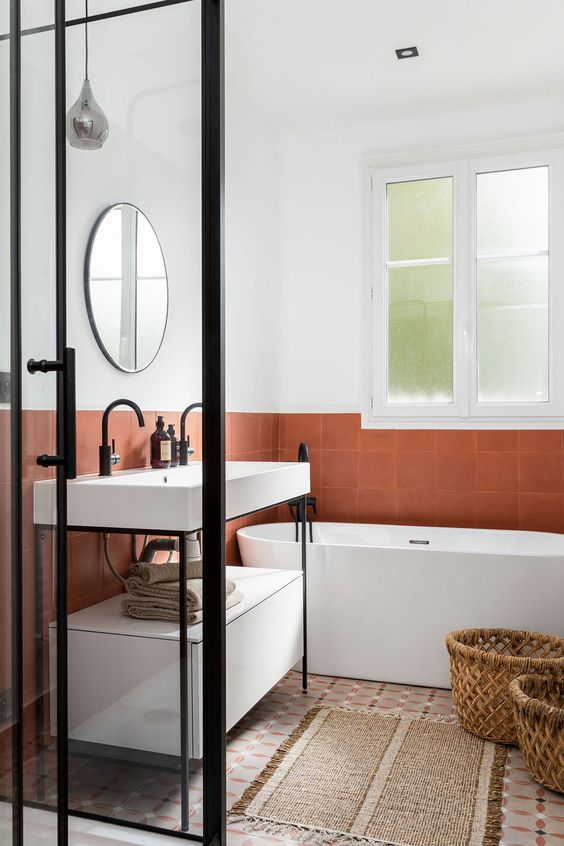 a stylish modern bathroom with white and rust-colored tiles, a console sink, an oval tub, a round mirror and a shower space enclosed in glass