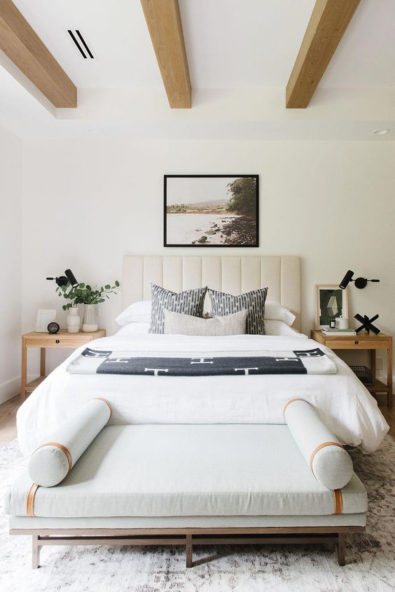 a stylish modern bedroom with light wooden beams, a neutral upholstered bed, a lovely daybed, light-stained nightstands and a cool artwork