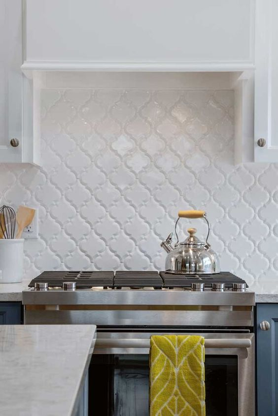 a stylish modern two-tone kitchen with white and navy cabinets, a white arabesque tile backsplash with white grout for an accent