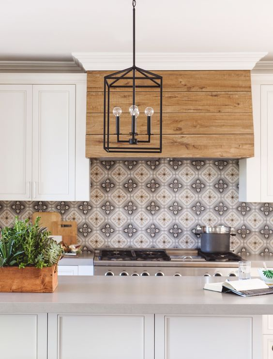 a stylish white farmhouse kitchen with a wooden hood, a pretty patterned tile backsplash, a white and grey kitchen island and a black pendant lamp