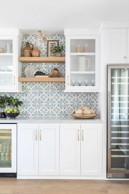 a stylish white kitchen with shaker cabinets, open shelves and blue Moroccan tiles on the backsplash is gorgeous