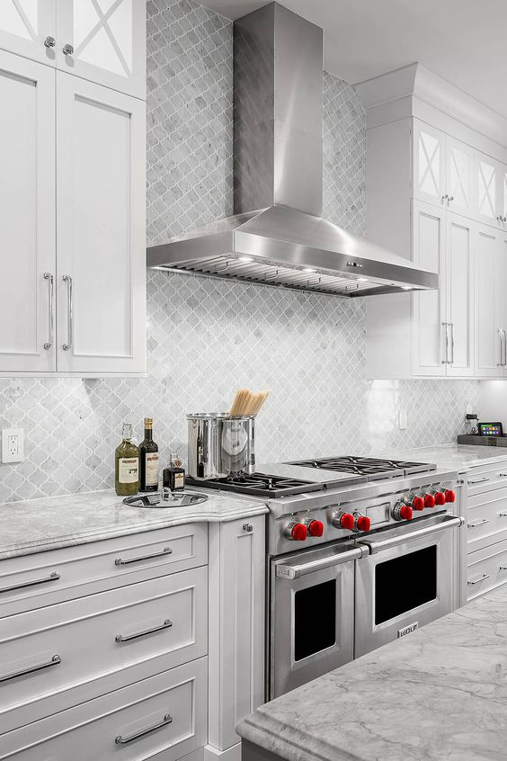 a stylish white kitchen with shaker style cabinets, grey stone countertops, a grey marble arabesque tile backsplash plus cool appliances