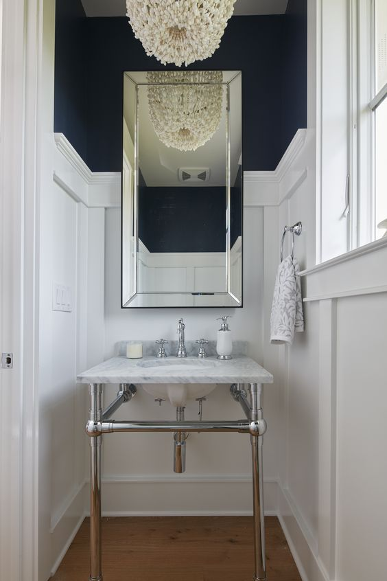 a super elegant coastal powder room with navy walls and white paneling, a console sink, a mirror and a beaded chandelier