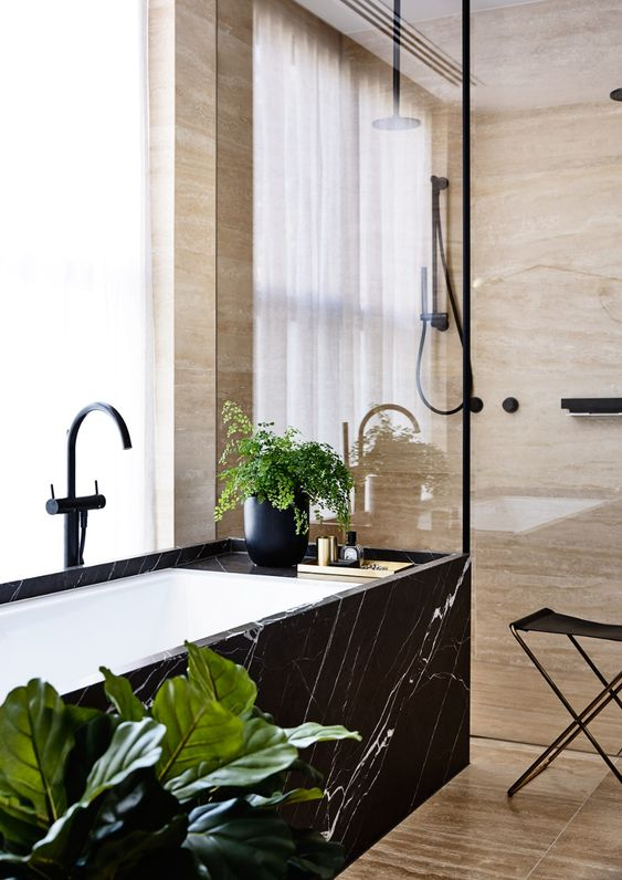 a tan stone bathroom with a shower space and a bathtub clad wiht black marble and black fixtures is a gorgeous space