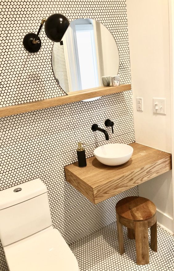 a tiny contemporary powder room clad with penny tiles, with a floating vanity and a stool, a round vessel sink and black fixtures
