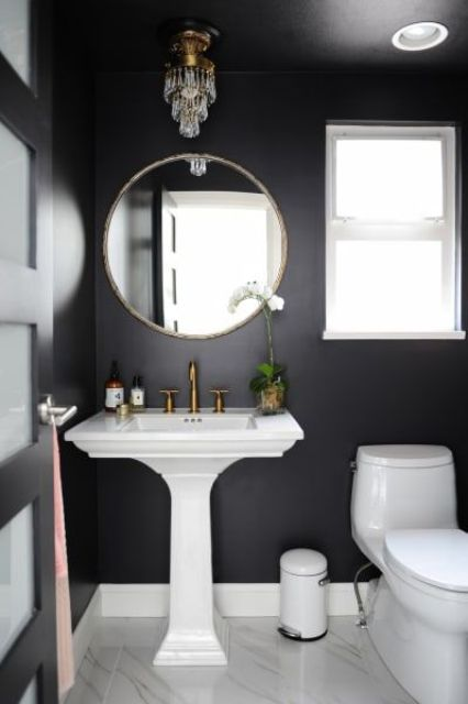 a tiny powder room with black walls, a pedestal sink, a round mirror, a crystal lamp and a potted bloom is a very cool solution