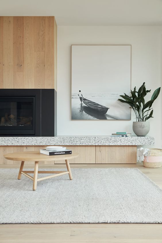 a trendy Japandi living room with sleek light-stained cabinets, an artwork, a neutral rug and a low coffee table plus a potted plant